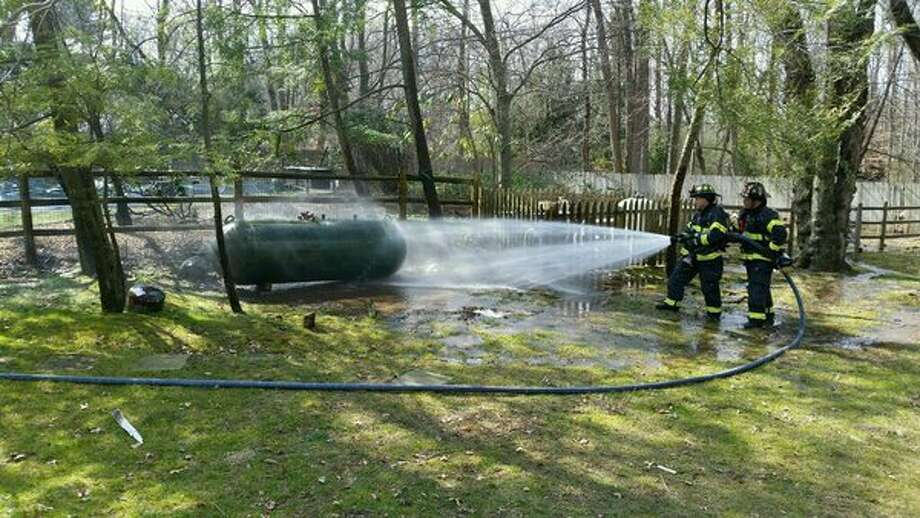 Firefighters hose down a propane tank with a leak in it. Photo: / Photo Courtesy Of Greenwich Fire Department