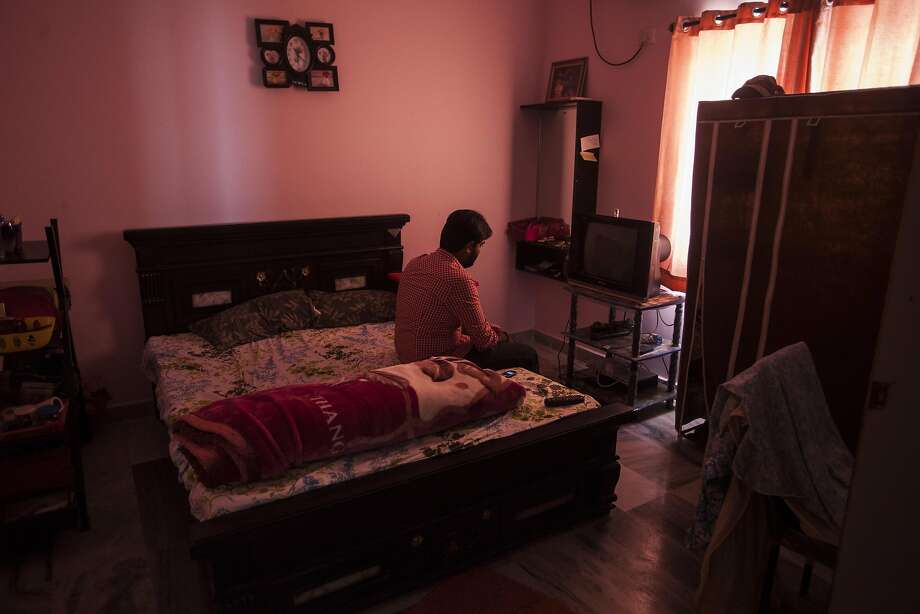A 30 year-old management consultant, who has been denied an H1-B visa waits for a work call in his bedroom. Photo: Photographer: Bernat Parera