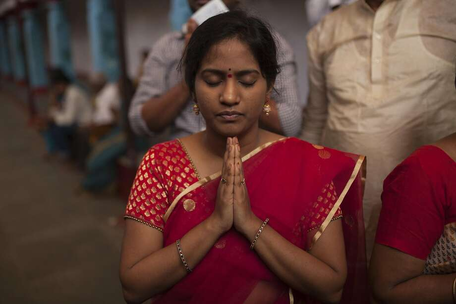 A devotee prays as she walks in the temple. Photo: Photographer: Bernat Parera