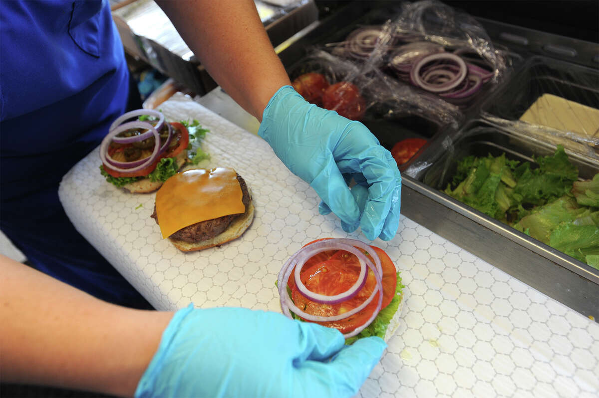 Food preps assemble a Boss Burger at Boss Burger on Twin City Highway in Nederland. Photo taken Tuesday, October 21, 2014 Guiseppe Barranco/@spotnewsshooter