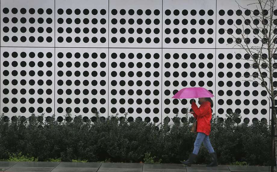 A woman walks in the rain past the Energy Biosciences Institute building in Berkeley, Calif. on Saturday, March 5, 2016 in the first of a series of major storms that are expected to drench the Bay Area. Photo: Paul Chinn Paul Chinn, The Chronicle