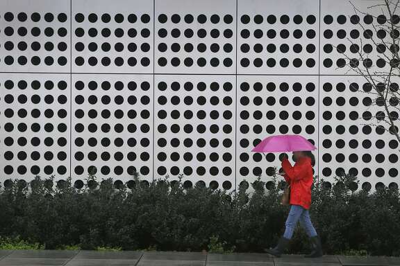 A woman walks in the rain past the Energy Biosciences Institute building in Berkeley, Calif. on Saturday, March 5, 2016 in the first of a series of major storms that are expected to drench the Bay Area.