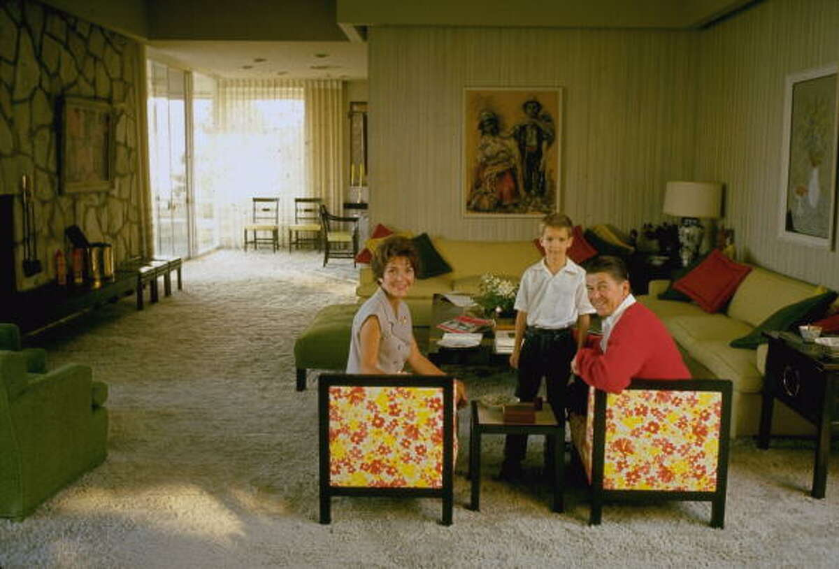 Ronald Reagan sitting with wife Nancy and son Ronnie at home in their living room.
