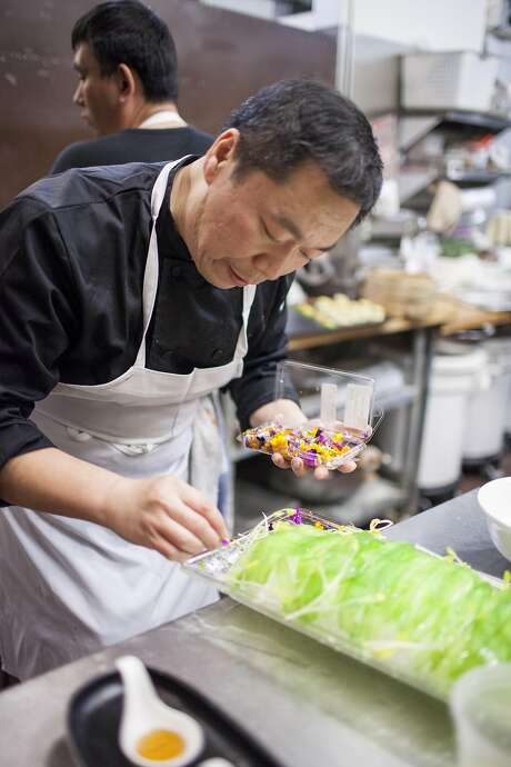 Chili House owner Li Jun Han puts the finishing touches on the bittermelon dish.  Photo: Peter Dasilva Peter Dasilva, Special To The Chronicle