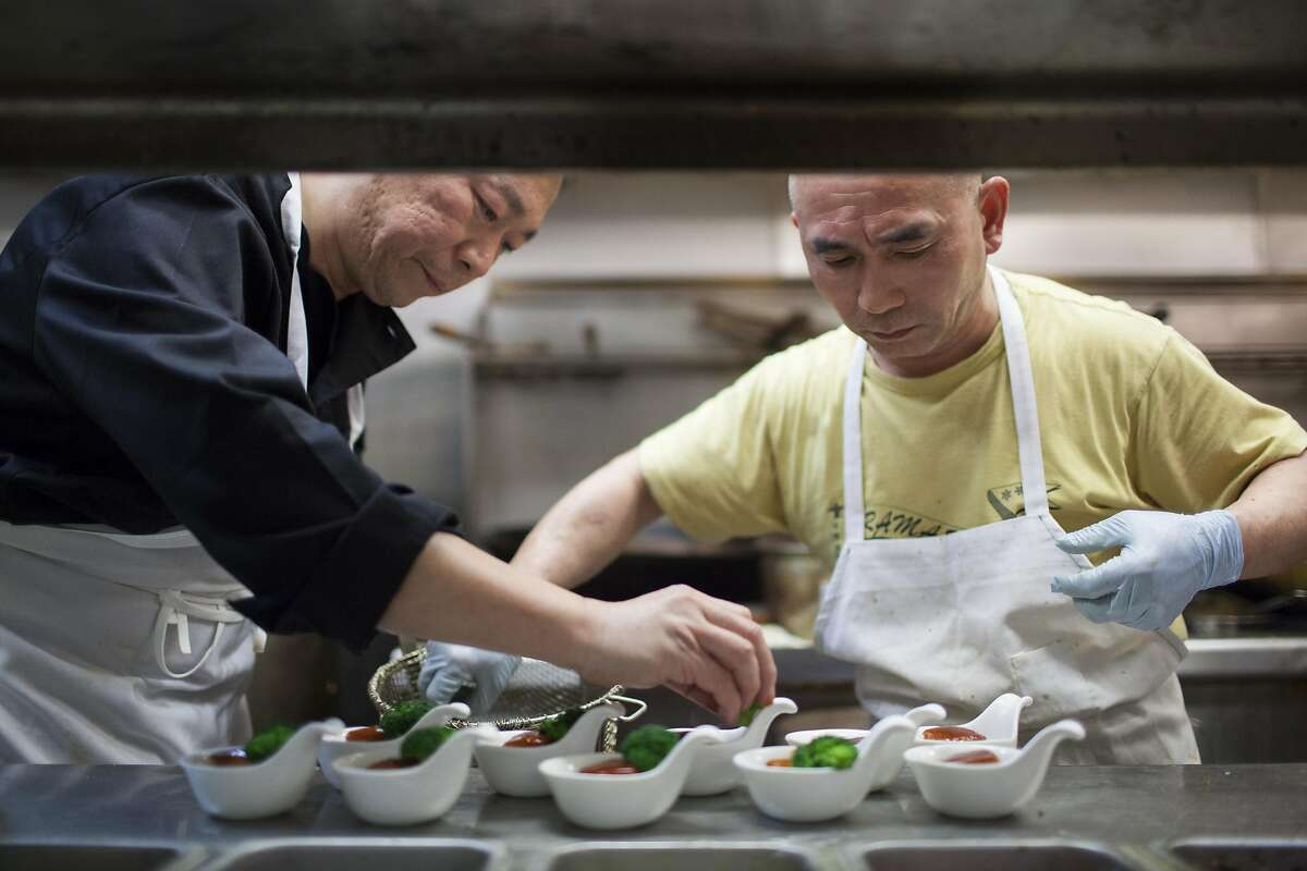 Chili House owner Li Jun Han (left) puts the finishing touches on pork belly braised Hangzhou-style, which is one of the Forbidden City banquet dishes at Chili House in San Francisco.