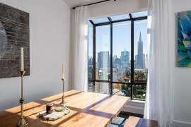 The top-floor great room features solarium windows in the dining area that frame landmark and skyline views.