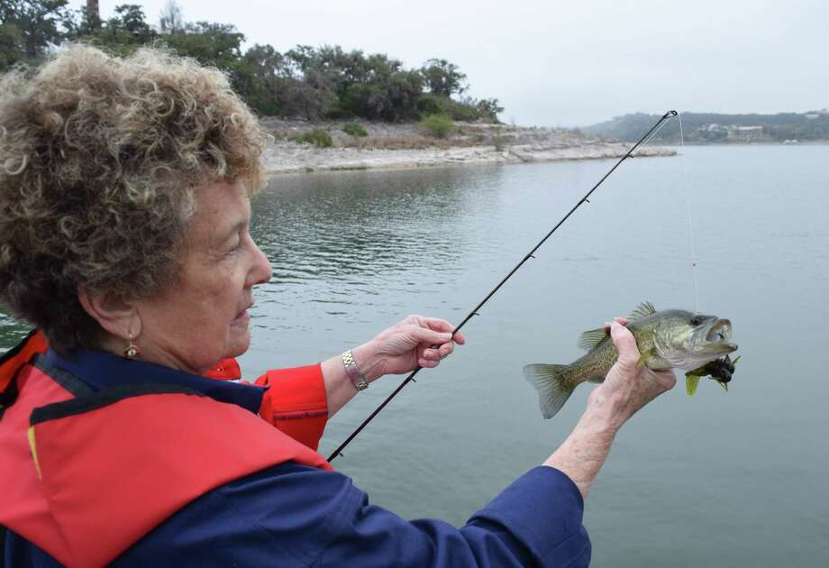 San Antonio boating safety instructor and avid angler Randi Wayland checks out an undersized largemouth bass she caught and then released during a recent fishing trip to Medina Lake. Photo: Photos By Ralph Winingham /For The Express-News