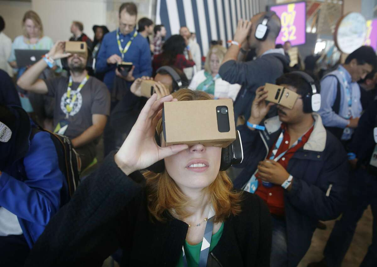 Jen Fitzpatrick, vice president engineering, and other attendees use Google Cardboard to try out the Expeditions app in a demo area during Google I/O 2015 conference at Moscone West on Thursday, May 28, 2015 in San Francisco, Calif.