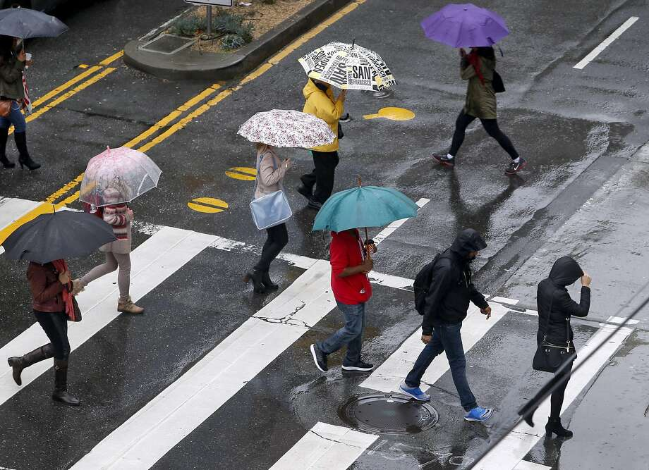 People are prepared for the rain as they cross Mission and Fourth streets in San Francisco, Calif. on Thursday, March 10, 2016. Photo: Paul Chinn Paul Chinn, The Chronicle