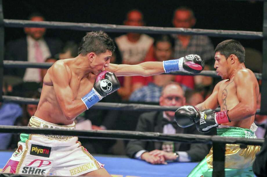 Mario Barrios, in white shorts, goes Sunday Sept. 6, 2015, against Jose Cen Torres, in green shorts, at the American Bank Center in Corpus Christi. Barrios won with a knock-out in the fourth round. Photo: Micah DeBenedetto / San Antonio Express-News / ©2015 San Antonio Express-News