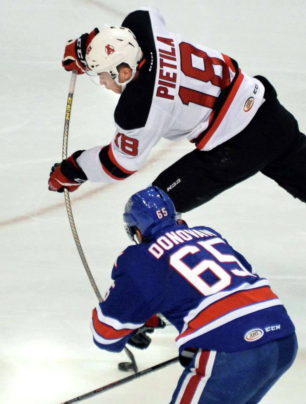 Albany Devils' #18 Blake Pietila, top, gets off a shot as Rochester Americans' #65 Matt Donovan defends during Saturday's game at the Times Union Center Dec. 5, 2015 in Albany, NY. (John Carl D'Annibale / Times Union)