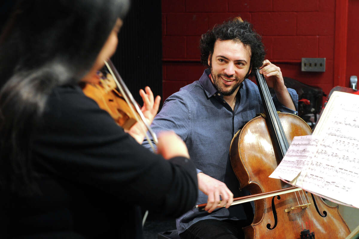 Eric Jacobsen, Conductor and Music Director for the Greater Bridgeport Symphony, plays the cello for students at Central High School, in Bridgeport, Conn. March 9, 2016. Jacobsen will lead the symphony this Saturday at the Klein Memorial when they perform Gustav Mahler?'s 5th Symphony.