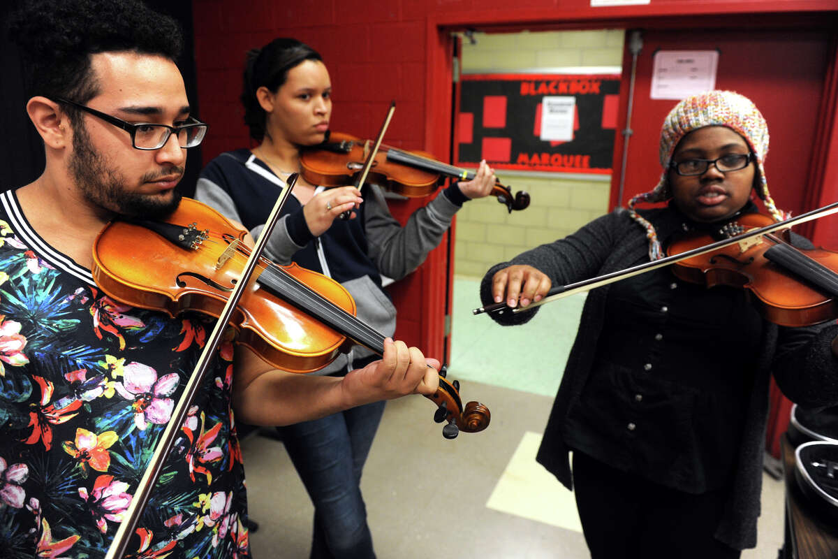 From left, Elvin Agosto, Sabrina Bazil and Donielle Daniels, all seniors, play their violins during a visit by Eric Jacobsen, Conductor and Music Director for the Greater Bridgeport Symphony during his visit to Central High School, in Bridgeport, Conn. March 9, 2016.