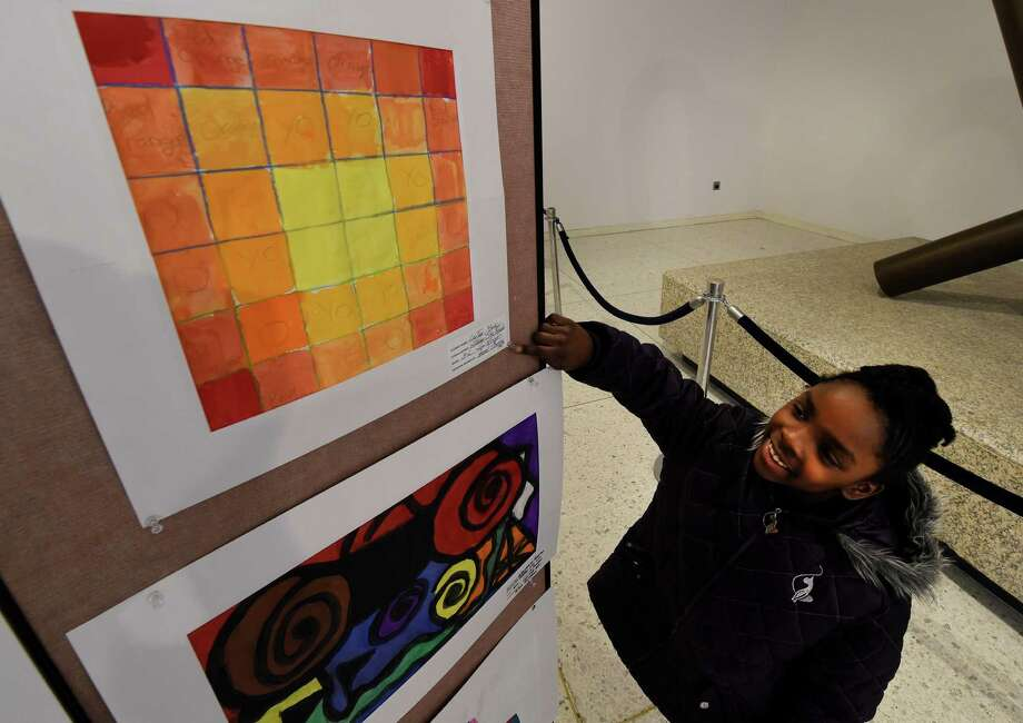 Lajay York, 8, of Thomas O'Brien Academy of Science and Technology in Albany is all smiles as she finds her artwork in the 7th Annual Student Exhibit featuring art inspired by the Empire State Plaza Art Collection on the concourse Thursday March 10, 2016 in Albany, N.Y.     (Skip Dickstein/Times Union) Photo: SKIP DICKSTEIN / 10035725A