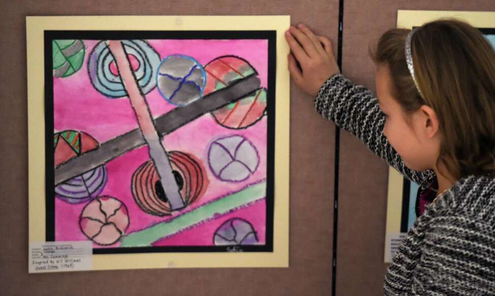Sofia Bodnaruk 8, of Shenendehowa's Chango Elementary School checks out her artwork in the 7th Annual Student Exhibit featuring art inspired by the Empire State Plaza Art Collection on the concourse Thursday March 10, 2016 in Albany, N.Y. (Skip Dickstein/Times Union)
