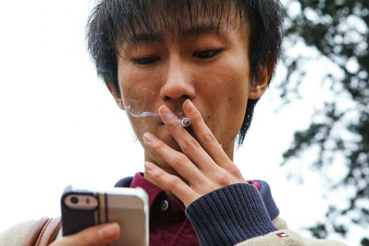 Yuto Takita takes a drag from his cigarette while on his cell phone, at UC Berkeley, in Berkeley, California, on Thursday, March 10, 2016.