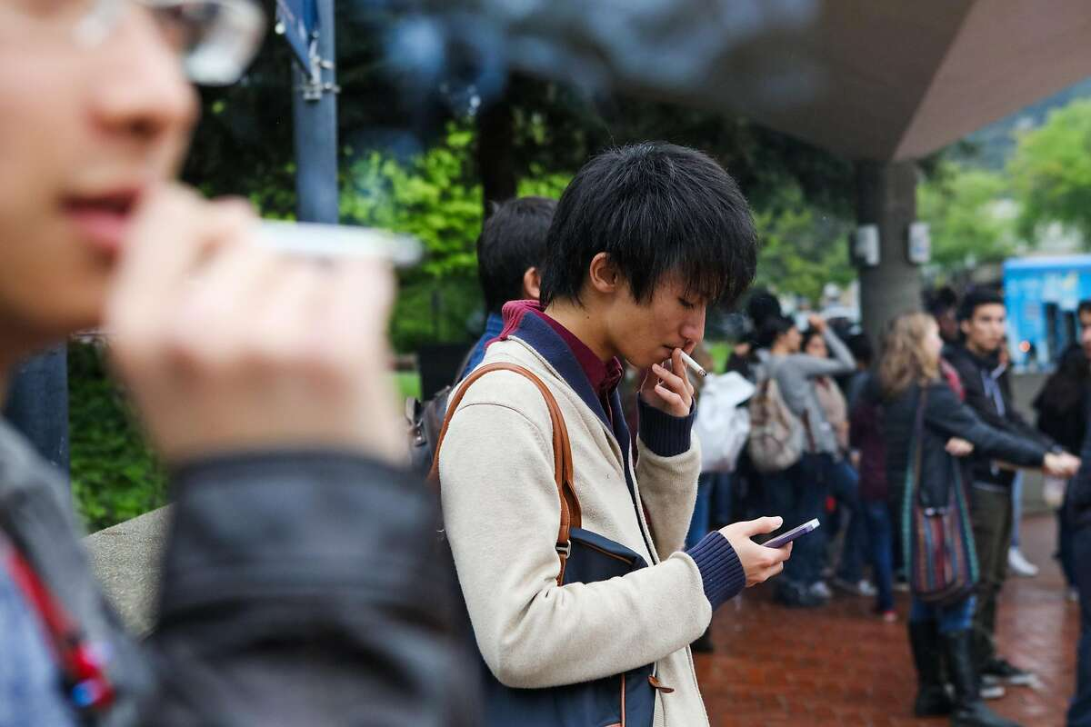 Yuto Takita, 23, (center) scrolls through his phone while smoking a cigarette at UC Berkeley, in Berkeley, California, on Thursday, March 10, 2016.