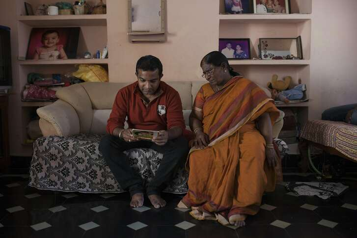 Sanjeev Reddy and his mother look at a family album in the house where Sanjeev grow up in Nalgonda.