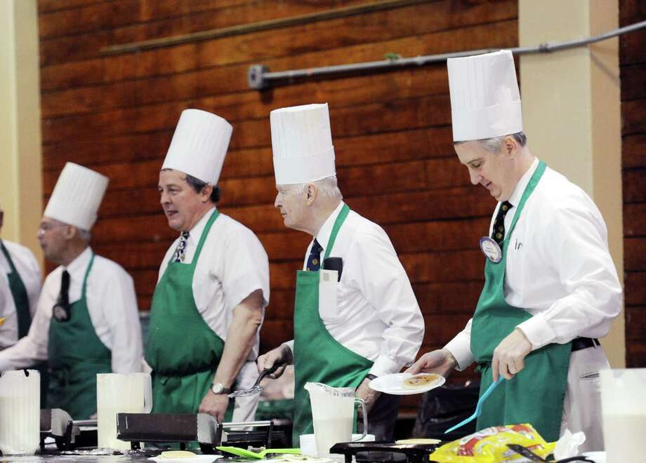 Old Greenwich Lions Club member Steve Tedesco, right, flips a pancake while working the grill with other club members during the Old Greenwich Lions Club 55th annual Pancake Fry at the Old Greenwich Civic Center last year. David Bonney, president of the Old Greenwich Lions Club, said that money raised from the event goes to more then 50 local organizations and charities that the club's supports. Bonney said the event is expected to raise between 8-10 thousand dollars for those organizations. Photo: Bob Luckey / Bob Luckey / Greenwich Time