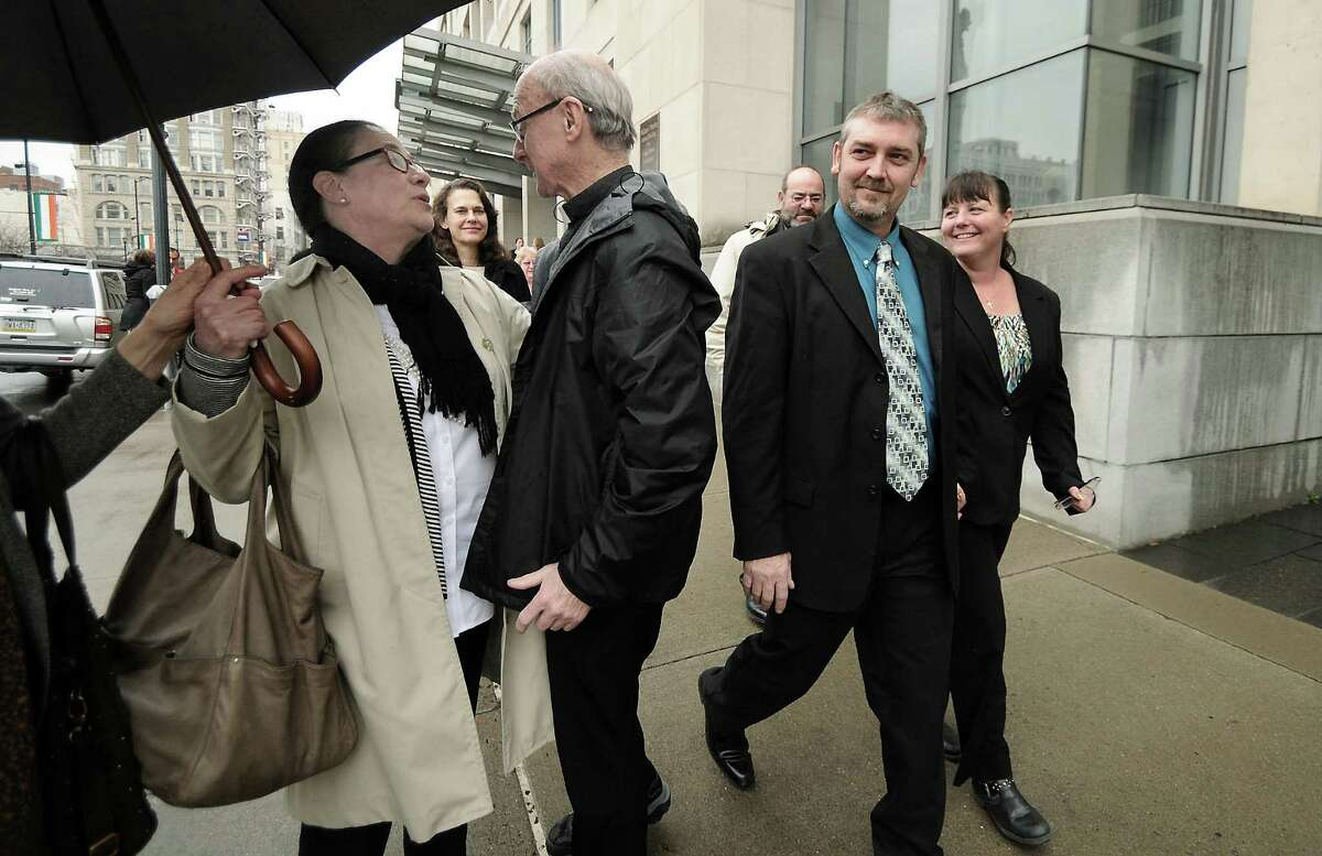 Dimock Township, Pa., residents Nolen Scott Ely and his wife Monica Marta-Ely, right, walks next to their lawyer Leslie Lewis as she chats with Reverend William B. Pickard on Thursday, March 10, 2016, in front of the William J. Nealon Federal Building and U.S. Courthouse in downtown Scranton, Pa., after the Ely's won their case against Cabot Oil & Gas based in Houston, Texas for $2.75 million dollars by a federal jury which held Cabot responsible for contaminating their well water with high levels of methane. Another family from Dimock Township, Pa., Raymond and Victoria Hubert were awarded $ 1.49 million dollars. Both families have been pursuing the case for 6 years after rejecting a settlement offer in 2012. ( Butch Comegys / The Times & Tribune via AP) MANDATORY CREDIT ORG XMIT: PASCR104