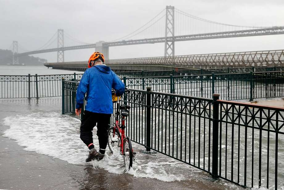 Bob Siegel walks with his bicycle through water from the bay spilling onto the sidewalk at Pier 14 along the Embarcadero during high tide in San Francisco, Calif. on Tuesday, Nov. 24, 2015. King tide conditions are causing higher than usual water levels. Photo: Paul Chinn, The Chronicle