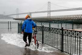 Bob Siegel walks with his bicycle through water from the bay spilling onto the sidewalk at Pier 14 along the Embarcadero during high tide in San Francisco, Calif. on Tuesday, Nov. 24, 2015. King tide conditions are causing higher than usual water levels.