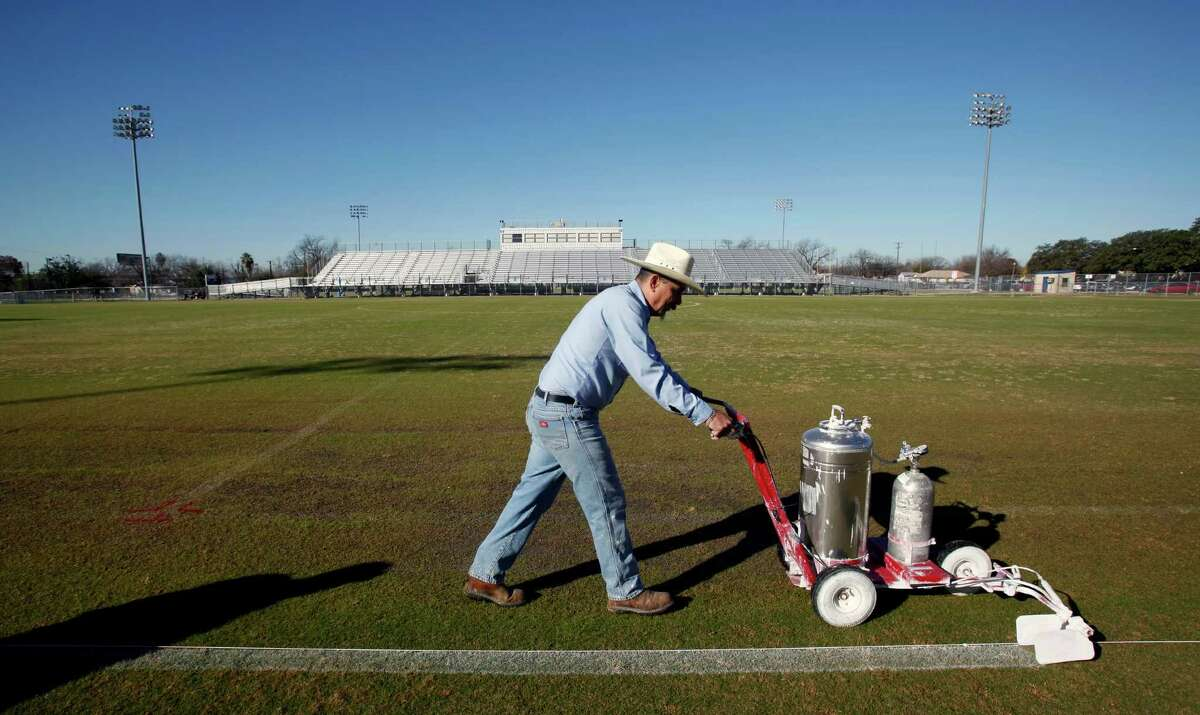 In this file photo, a San Antonio Independent School District athletics department maintenance worker Daniel Thatcher paints stripes on a field at the SAISD sports complex. Community activists are pushing the district to pay all workers a living wage.