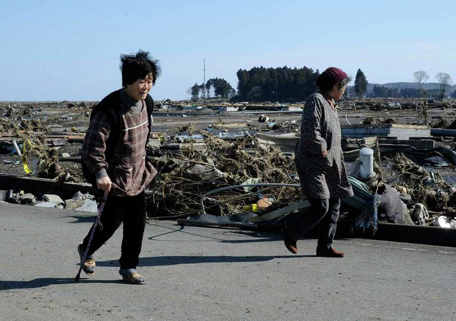 Residents wander through debris brought on by the tsunami in Japan on March 12, 2011. Five years later, the Japanese coast guard resumes the search for over 2,500 people who are still missing. Photo: TORU YAMANAKA, Staff / AFP