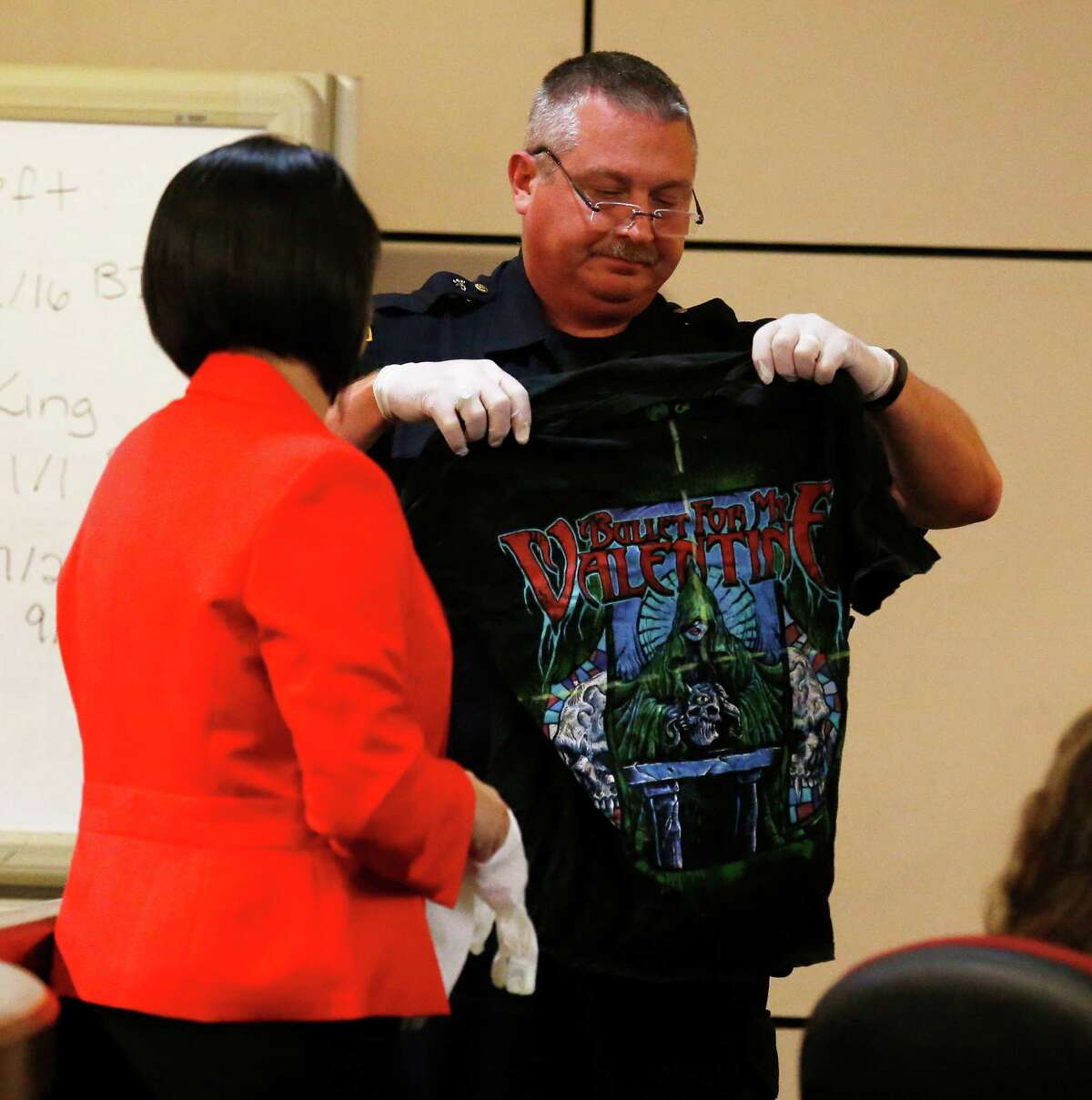 San Antonio Police Sgt. Ricky David Lopez (center) holds up a shirt belonging to murder victim Daniel Lee Cantu during questioning from prosecutor Kimberly Gonzalez during the Anthony Lee Smith murder trial in the 186th State District Court with Judge Jefferson Moore presiding on Thursday, Mar. 10, 2016. Smith is alleged to have shot Cantu and the shirt appeared to be marked with yellow-dashed lines to indicate the entry point of the bullet wound. (Kin Man Hui/San Antonio Express-News)