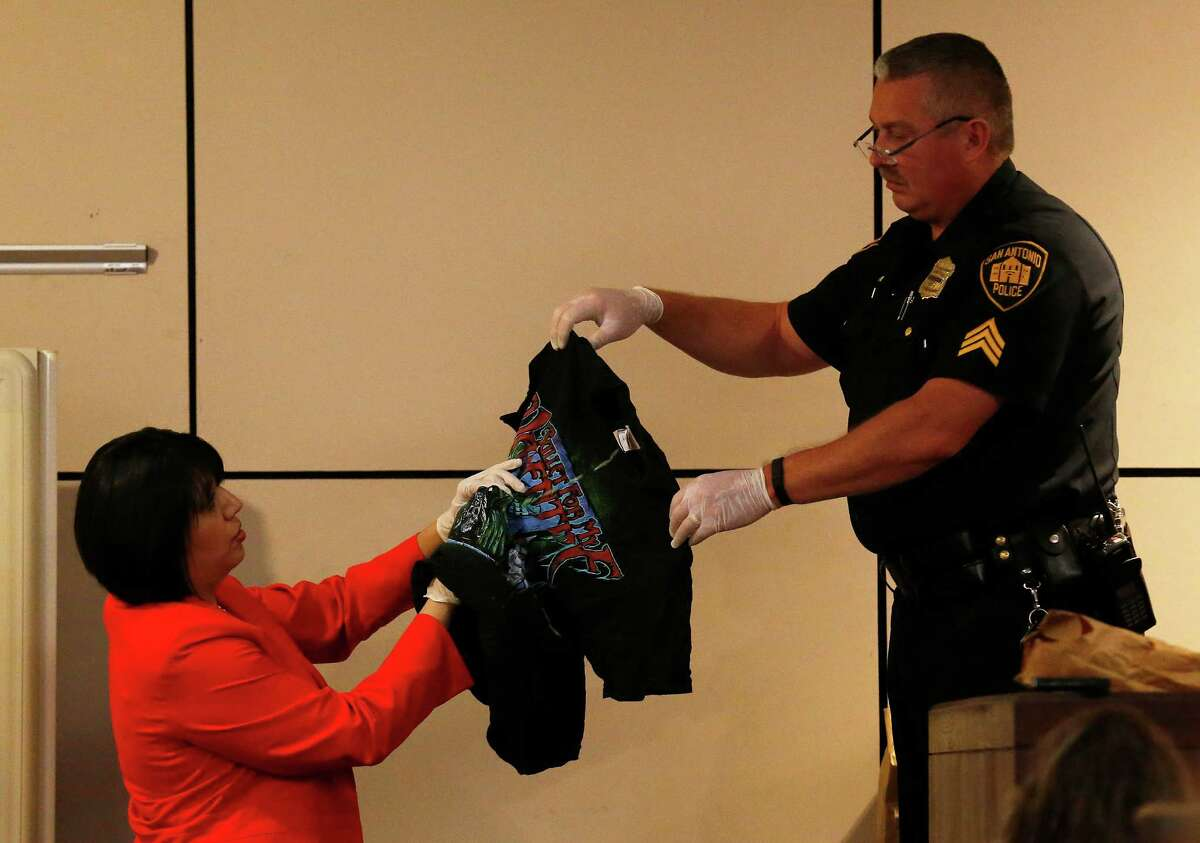 San Antonio Police Sgt. Ricky David Lopez (right) holds up a shirt belonging to murder victim Daniel Lee Cantu during questioning from prosecutor Kimberly Gonzalez (left) during the Anthony Lee Smith murder trial in the 186th State District Court with Judge Jefferson Moore presiding on Thursday, Mar. 10, 2016. Smith is alleged to have shot Cantu and the shirt is marked with yellow-dashed lines to indicate the entry point of the bullet wound. (Kin Man Hui/San Antonio Express-News)