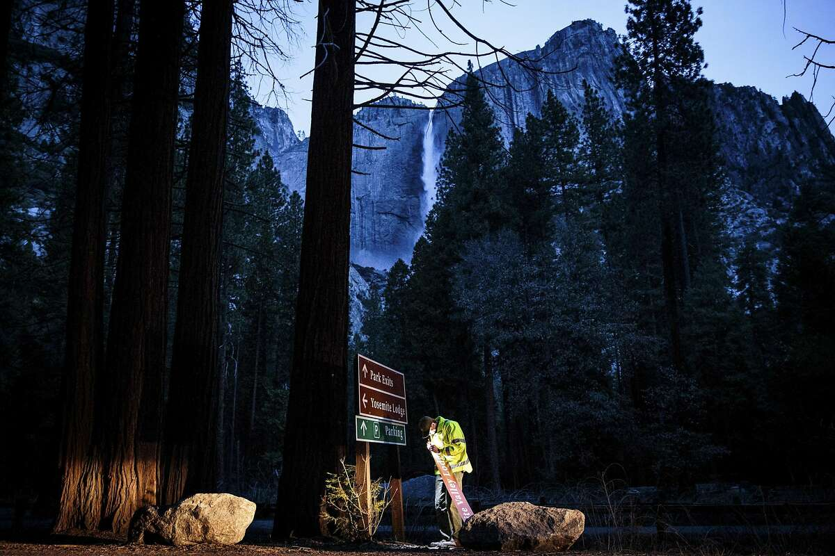 Josh Alsup, a park service mechanic, works to cover a Yosemite Lodge road sign with one that reads Yosemite Valley Lodge, at Yosemite National Park in California, March 1, 2016. Delaware North, a company that until recently ran the park�s hotels, restaurants and shops, has caused an uproar by having apparently successfully trademarked the name Yosemite National Park. (Max Whittaker/The New York Times)