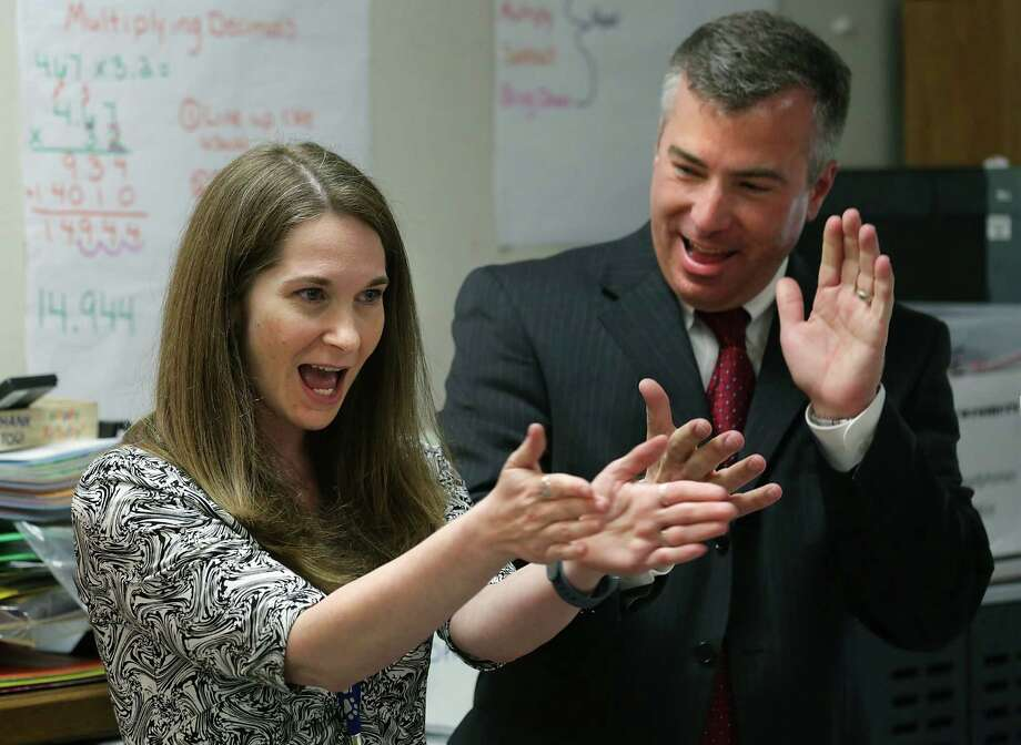 Sarah Aguirre, left, a teacher at Colonies North Elementary School, and Dr.Brian Woods, NISD Superintendant, react after she was named a finalist for the 2016 HEB Excellence in Education Awards, on Monday, March 7, 2016.  She teaches children of refugees that have settled in San Antoino. Photo: Bob Owen, Staff / San Antonio Express-News / San Antonio Express-News