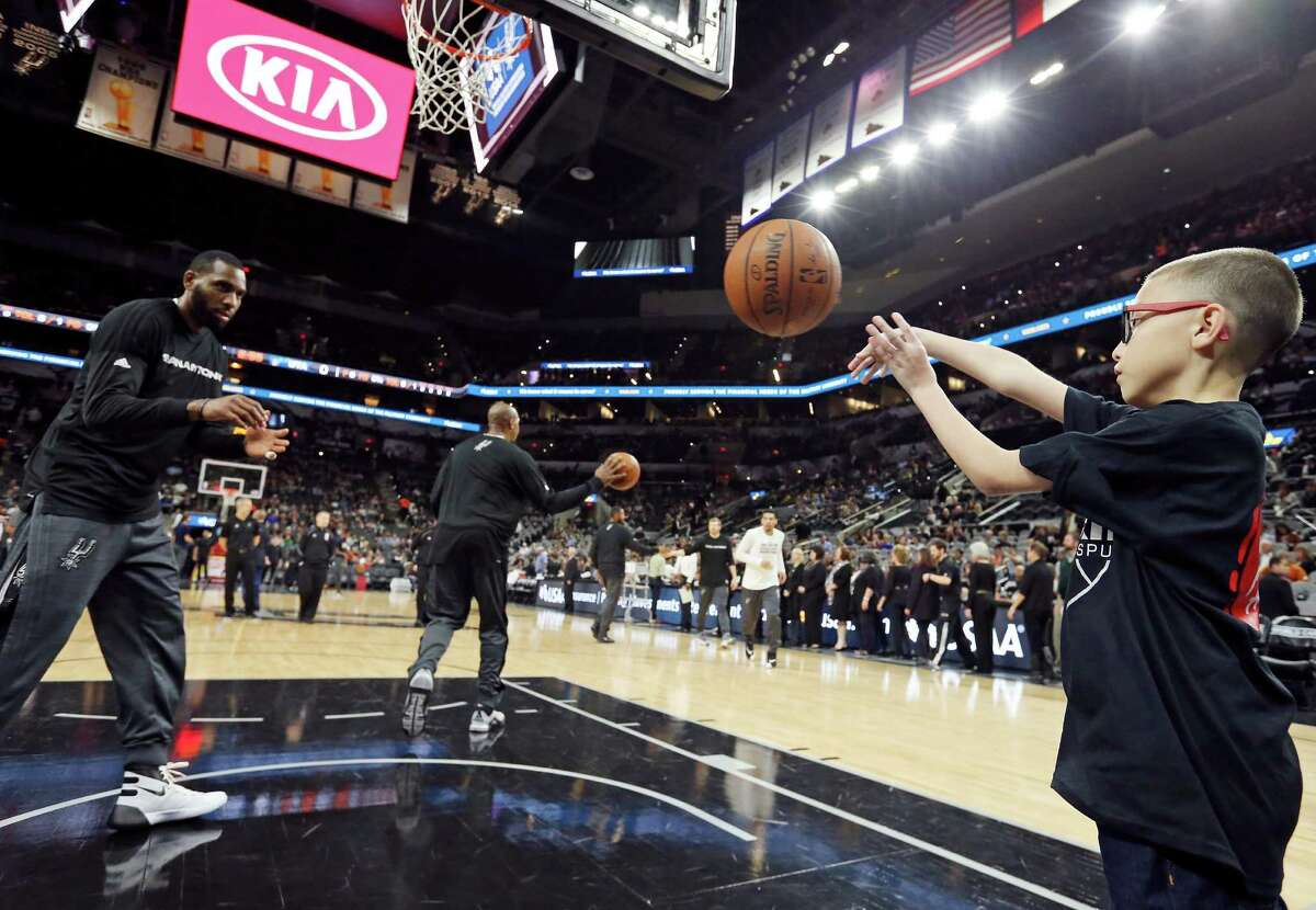 Ginobili San Miguel-Ramirez, 10, throws the ball to San Antonio Spurs' Rasual Butler during warmups before the game with the Utah Jazz Monday Dec. 14, 2015 at the AT&T Center.