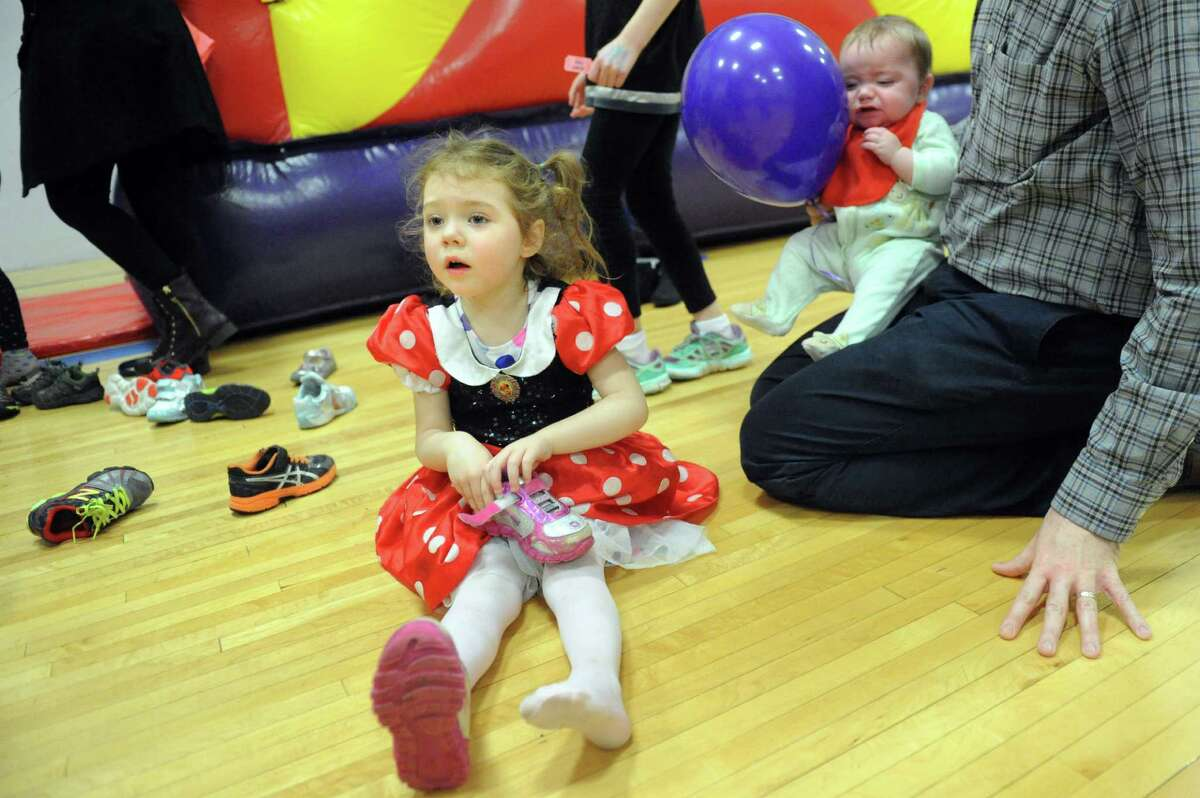 Lucy Walden, 3, of Albany puts her shoes back on after fun in a bounce house during the Purim Carnival on Thursday, March 10, 2016, at Albany Jewish Community Center in Albany, N.Y. Joining her are little sister, Lizzi, 7 months, right, and father, Brian. The event featured food, games and face painting. Purim is a joyous Jewish holiday that commemorates a time when the Jewish people living in Persia were saved from extermination. (Cindy Schultz / Times Union)