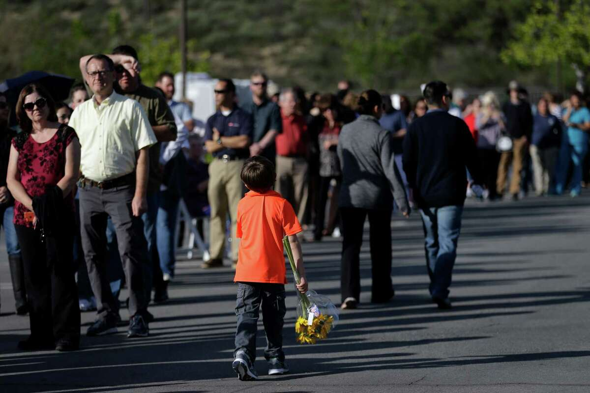 People wait in line to board buses to take them to the Ronald Reagan Presidential Library for the public viewing of former First Lady Nancy Reagan Wednesday, March 9, 2016, in Simi Valley, Calif. (AP Photo/Jae C. Hong) ORG XMIT: CAJH102