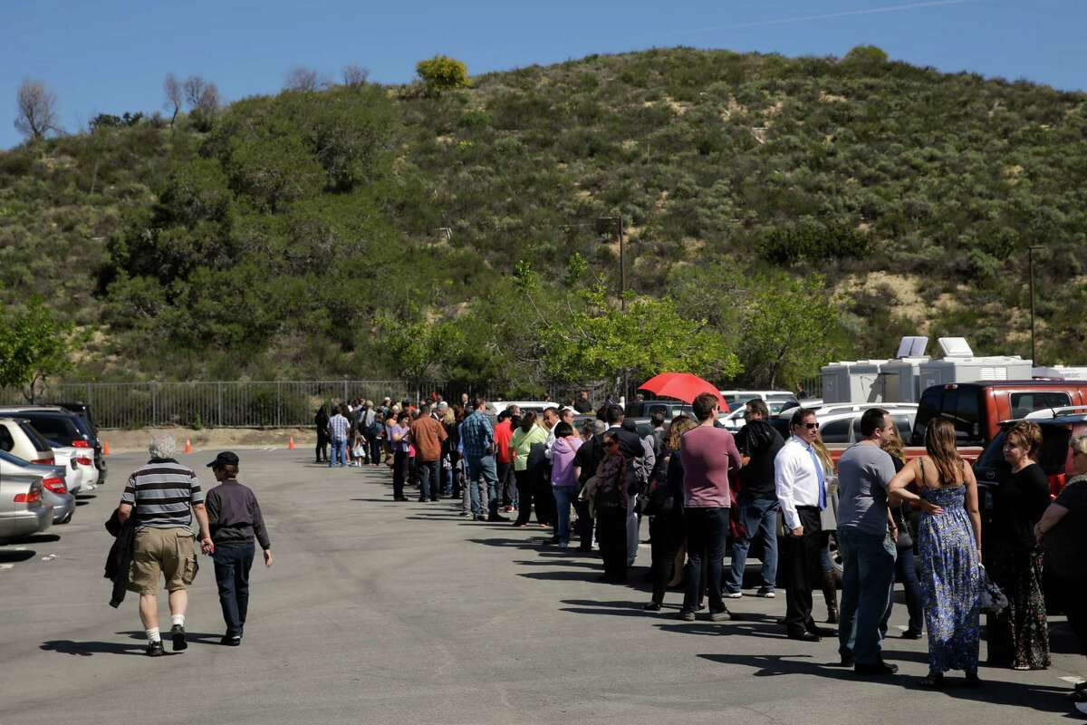 People wait in line to board buses to take them to the Ronald Reagan Presidential Library for the public viewing of former First Lady Nancy Reagan Thursday, March 10, 2016, in Simi Valley, calif. (AP Photo/Jae C. Hong) ORG XMIT: CAJH101