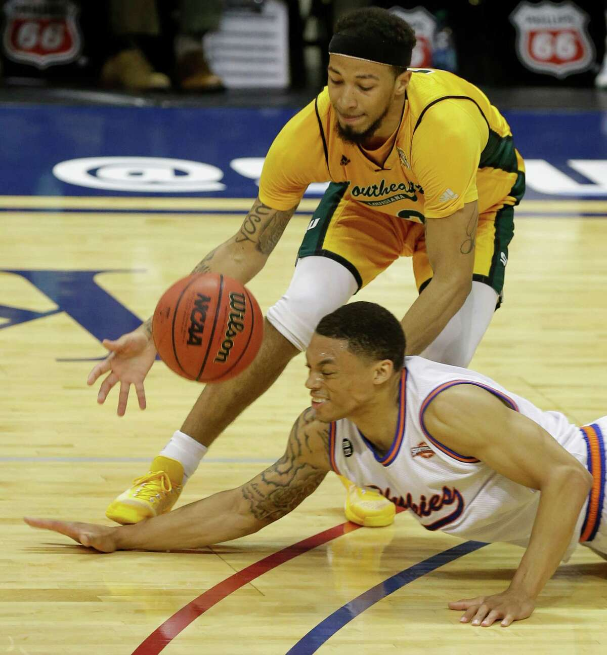 Southeastern Louisiana Dimi Cook and Houston Baptist Caleb Crayton scramble for the ball during the second of game at the Southland conference tournament Thursday, March 10, 2016, in Katy.