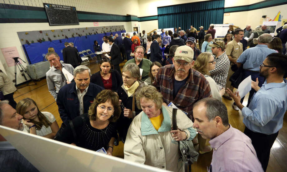 People look at a photo of a Chesapeake, Va., military facility after contaminated water was found. Photo: Steve Earley /Associated Press / The Virginian-Pilot