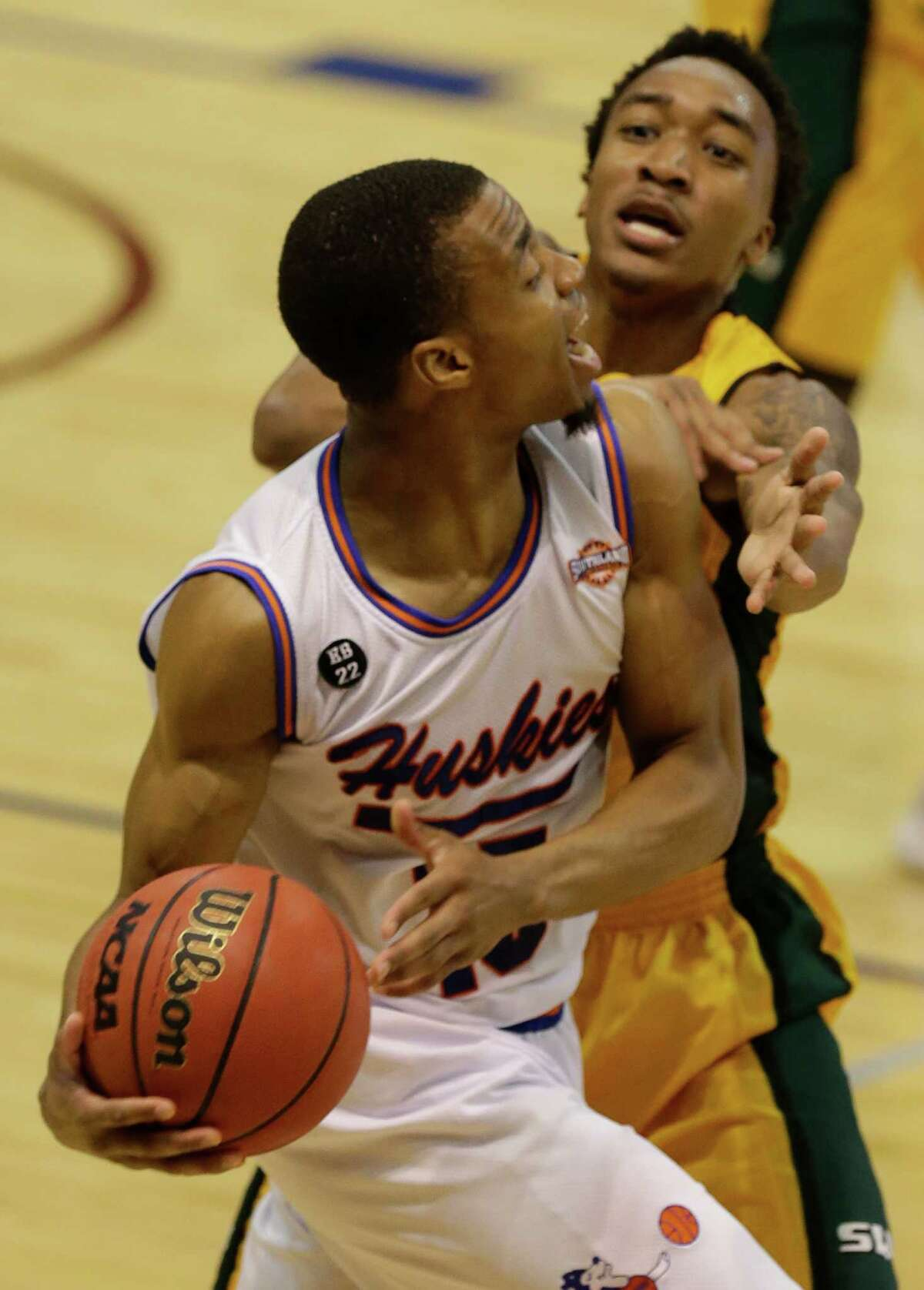 Houston Baptist Reveal Chukwujekwu looks to pass around Southeastern Louisiana Joshua Filmore during the second of game at the Southland conference tournament Thursday, March 10, 2016, in Katy.
