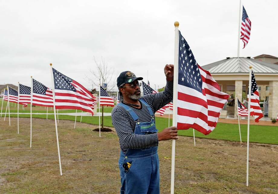Mark Hyde, of the Exchange Club of Killeen, adjusts one of the 490 U.S. flags around the memorial to those killed and wounded Nov. 5, 2009, at Fort Hood. Photo: Edward A. Ornelas, Staff / © 2016 San Antonio Express-News