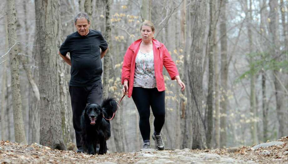 Jacob and Kristin Berman, of Old Greenwich, walk their dog, Joey, Thursday on the trails at Mianus River Park in Stamford. Photo: Matthew Brown / Hearst Connecticut Media / Stamford Advocate