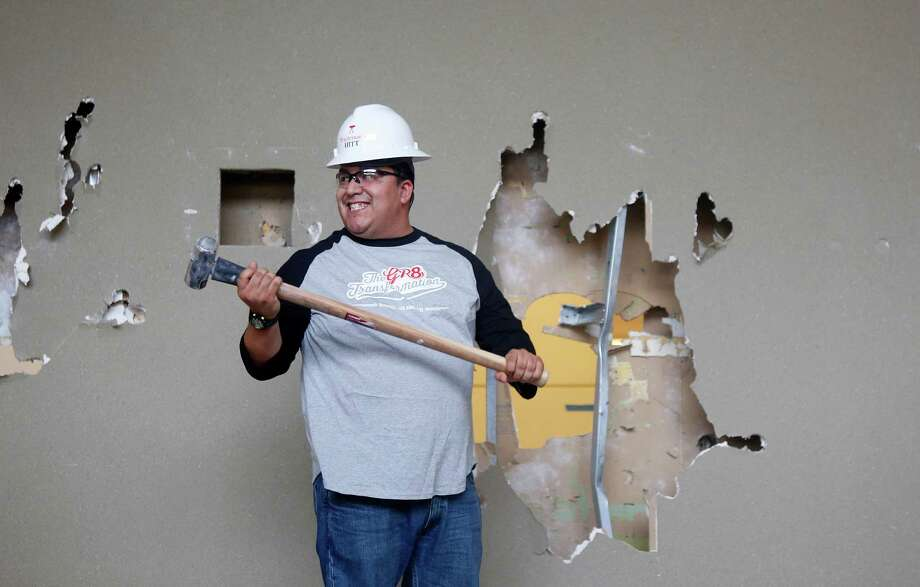 Mario Sierra is all smiles after taking a swing Thursday at a wall at the future headquarters of Mattress Firm. Sierra works in the digital department.  Photo: Mark Mulligan, Staff / © 2015 Houston Chronicle