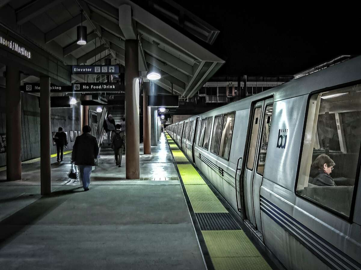 Commuters and train riders at the Concord/Martinez BART station at nighttime.