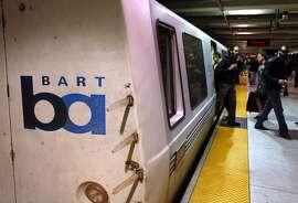 Bay Area Rapid Transit passengers walk off of a train in San Francisco.