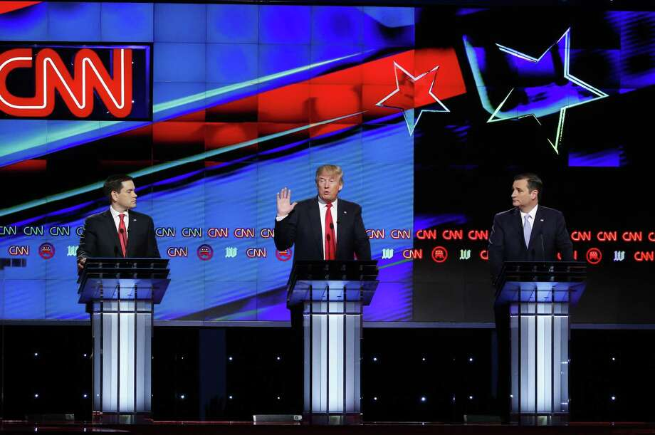 Republican presidential candidate, businessman Donald Trump, center, speaks as candidates, Sen. Marco Rubio, R-Fla., left, and Sen. Ted Cruz, R-Texas, right, listen, during Thursday's Republican presidential debate at the University of Miami in Coral Gables, Fla. Photo: Wilfredo Lee, AP / AP