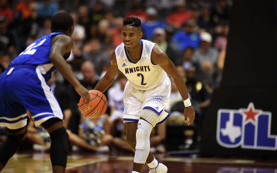 Elkins guard Ken Busby, right, sizes up Fort Worth Dunbar's Tobias Phillips during the Class 5A semifinals Thursday night at the Alamodome. Busby topped six Knights in double figures with 21 points. Photo: Jerry Baker Jerry Baker, Freelance