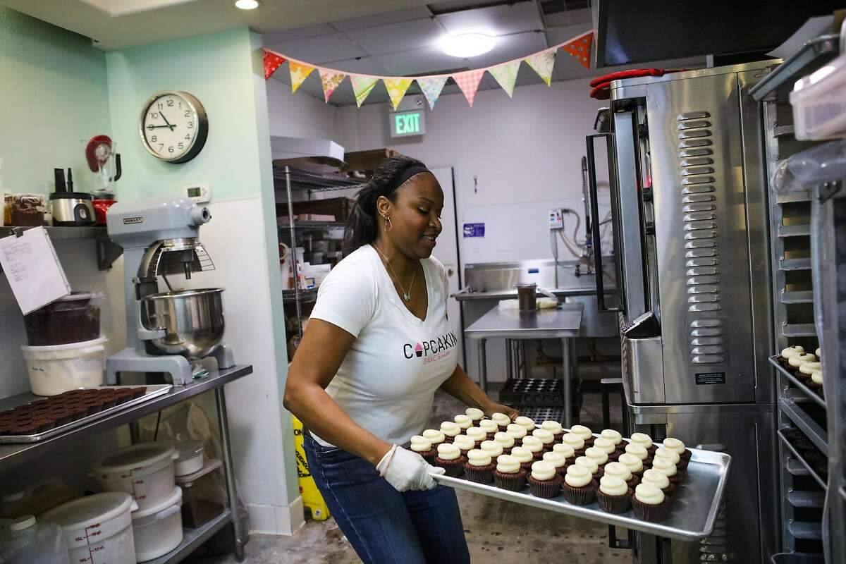 Owner Lila Owens grabs a fresh batch of red velvet cupcakes to decorate, at Cupcakin' Bake Shop in Berkeley, California, on Thursday, March 10, 2016.