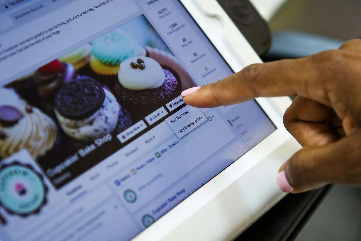 Owner Lila Owens looks at incoming messages on the stores Facebook page, at Cupcakin' Bake Shop, in Berkeley, California, on Thursday, March 10, 2016.