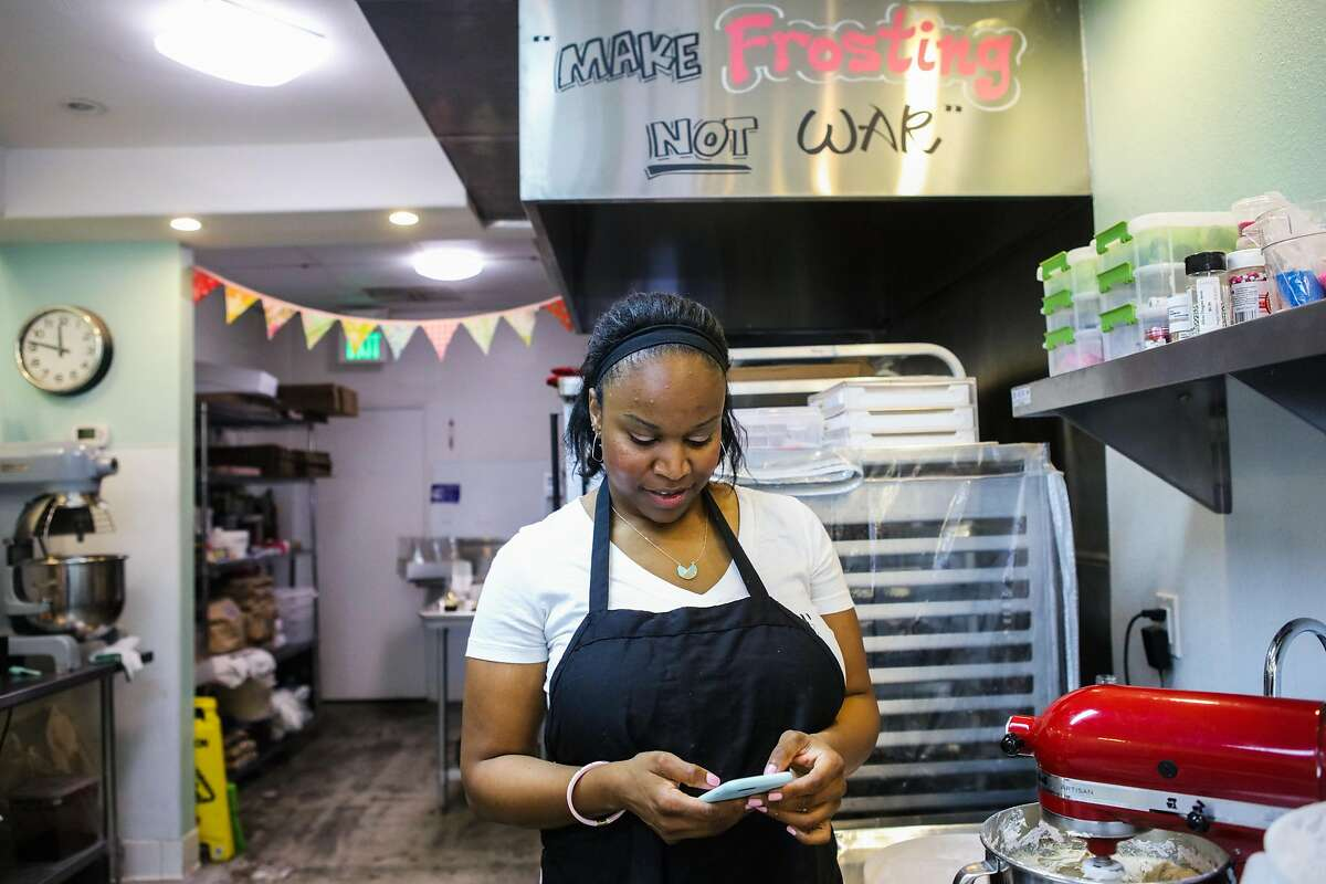 Store owner Lila Owens (center) checks her phone to see if she has any incoming messages on the store Facebook page, at Cupcakin' Bake Shop in Berkeley, California, on Thursday, March 10, 2016. The Facebook page allows customers to message the store directly to order cupcakes.