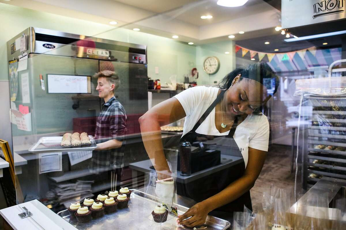 Owner Lila Owens (right) fills bags of cupcakes for a wedding order while baker Darcy Hay carries a tray of freshly baked cupcakes, at Cupcakin' Bake Shop, in Berkeley, California, on Thursday, March 10, 2016.